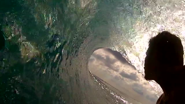 pov view of a surfer surfing inside waves and getting tubed on a surfboard. - slow motion - chance stock videos & royalty-free footage