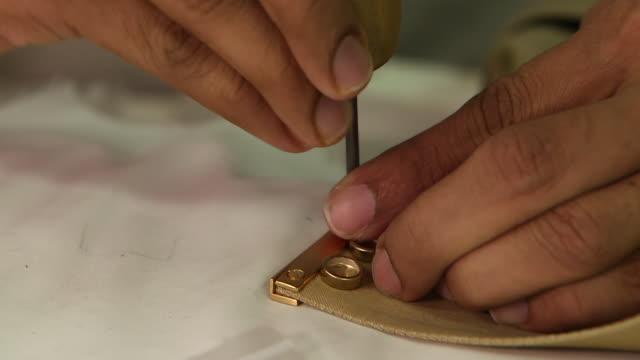 view of a tailor's hands screwing metal rods at the end of a man's belt. - jiddah bildbanksvideor och videomaterial från bakom kulisserna
