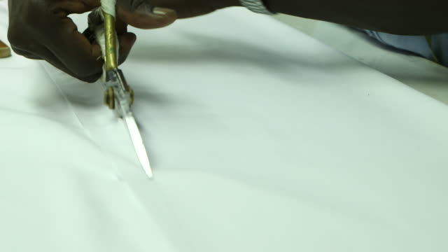 view of a tailor's hands using scissors to cut fabric. - jiddah stock-videos und b-roll-filmmaterial