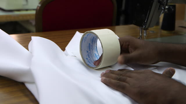 view of a tailor's hands using sticky tape to remove lint from a traditional arab thobe - tape measure stock videos & royalty-free footage