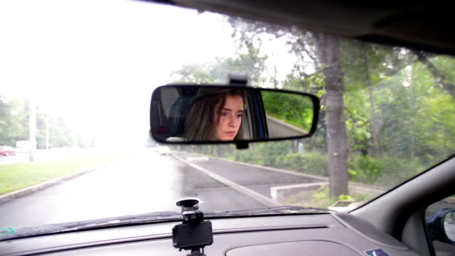 view of a teenager in the car mirror - driver's license stock videos and b-roll footage