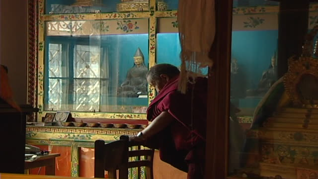 view of a tibetan sarvastivada monk praying. the primary purpose of the library is to provide a cultural resource and promote research. - skåp med glasdörrar bildbanksvideor och videomaterial från bakom kulisserna