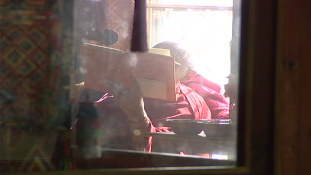 view of a tibetan sarvastivada monk through a glass display case reading the library houses over 80000 tibetan manuscripts and books - präsentation hinter glas stock-videos und b-roll-filmmaterial