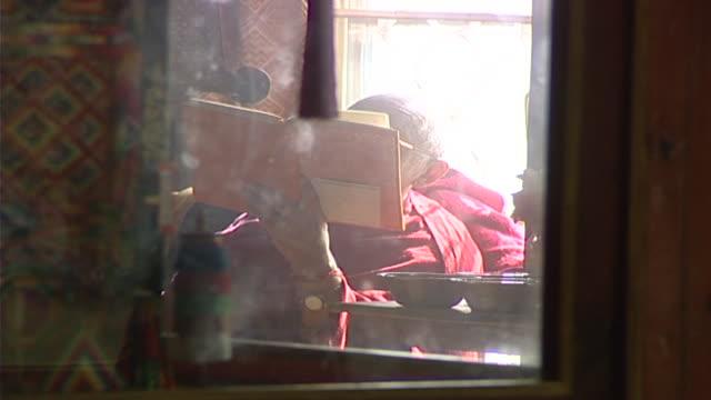 view of a tibetan sarvastivada monk, through a glass display case, reading. the library houses over 80,000 tibetan manuscripts and books. - skåp med glasdörrar bildbanksvideor och videomaterial från bakom kulisserna