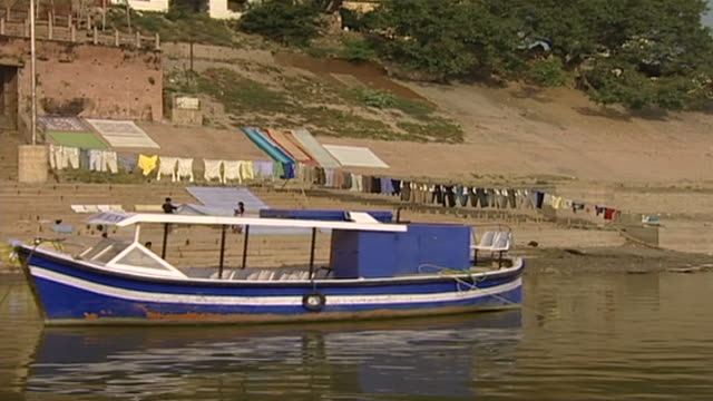 view of a tourist boat anchored next to the prahalada ghat in varanasi - anchored stock videos & royalty-free footage