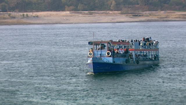 vídeos de stock e filmes b-roll de view of a tourist ferry boat coming in to dock on the nile in luxor. - embarcação comercial