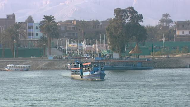 vídeos de stock e filmes b-roll de view of a tourist ferry boat crossing on the nile in luxor. - embarcação comercial