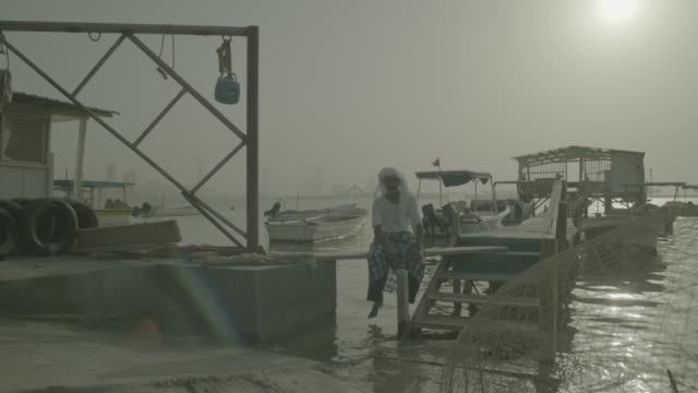 vidéos et rushes de view of a traditional bahraini fisherman sitting on a wooden pier above the gulf sea - coiffe traditionnelle