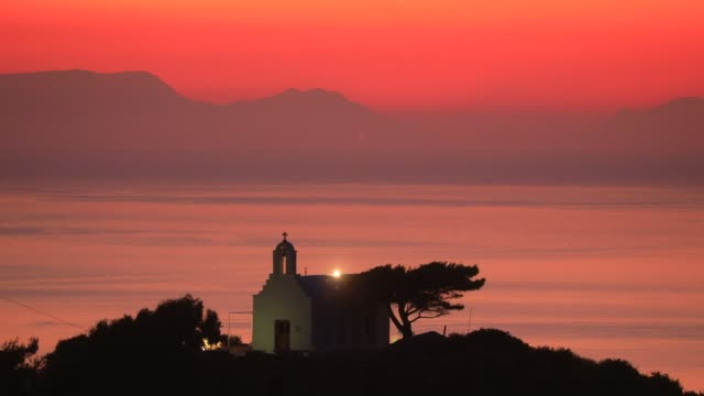 view of a traditional orthodox chapel above a hill in the early morning, as warm colors fill the sky in lefkes mountain village on august 19, 2020 in... - christentum stock-videos und b-roll-filmmaterial