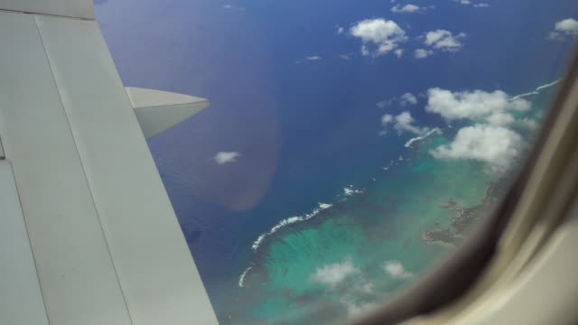 View of a tropical island from airplanes window during flight