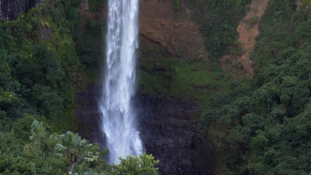 view of a tropical waterfall hitting the rocks - mgost stock videos and b-roll footage