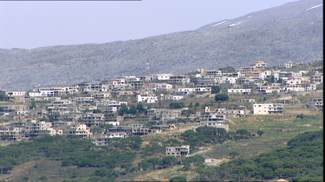 stockvideo's en b-roll-footage met view of a village perched on foothill beneath snow-capped mount hermon which straddles the border between syria and lebanon. - benen gespreid