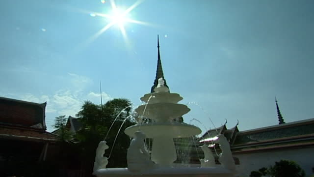 view of a white marble fountain in the grounds of the temple. - temple building stock videos & royalty-free footage