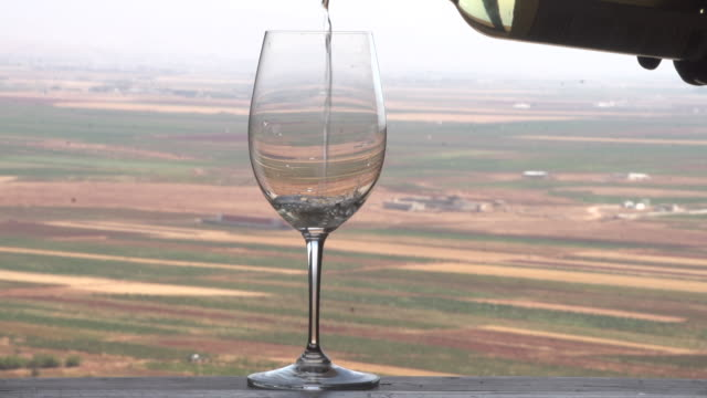view of a wine glass being filled with white wine set against a view of the beqaa valley in lebanon. - wine glass stock videos & royalty-free footage