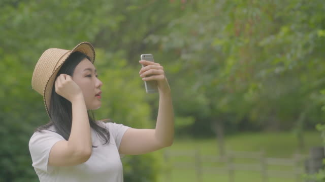 view of a woman fixing her hair with a smartphone at a park - mid length hair stock videos & royalty-free footage