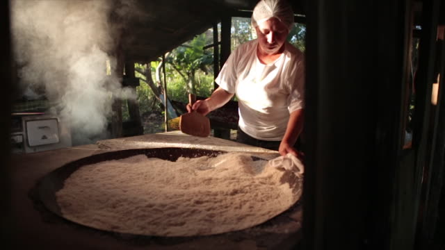 vídeos de stock, filmes e b-roll de view of a woman processing manioc flour (three clips edited) - traveling movement - moinho