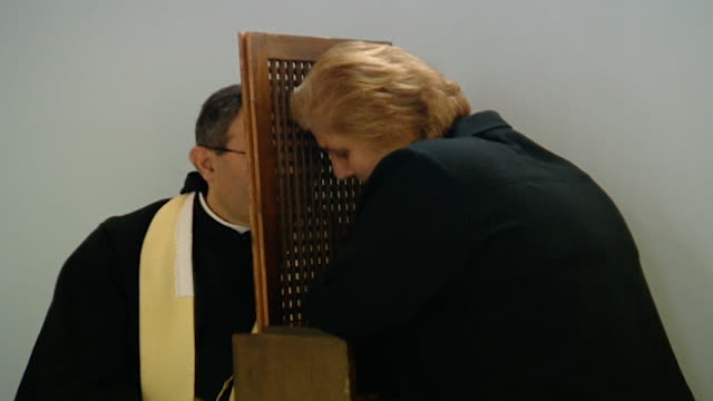 view of a woman receiving the sacrament of penance or confession in the maronite church. - 懺悔点の映像素材/bロール