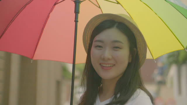 stockvideo's en b-roll-footage met view of a woman smiling with a colorful umbrella on rainy day - middellang haar