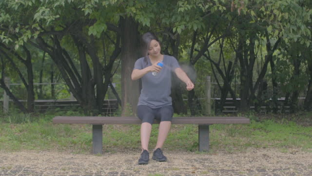 view of a woman spraying mosquito repellents on her arms and legs - 虫除け点の映像素材/bロール