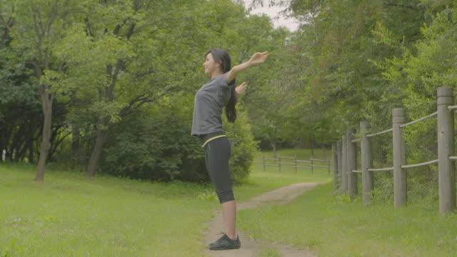 vídeos y material grabado en eventos de stock de view of a woman stretching out after running at a park - cabello recogido