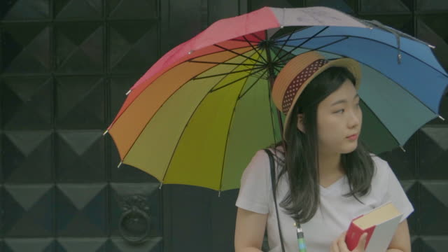 view of a woman taking brief shelter from the rain - mid length hair stock videos & royalty-free footage