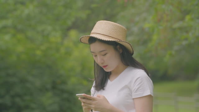 view of a woman using a smartphone at a park - mid length hair stock videos & royalty-free footage