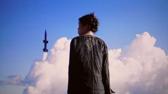 view of a woman with a missile taking off in the background. - nuclear missile launch stock videos & royalty-free footage