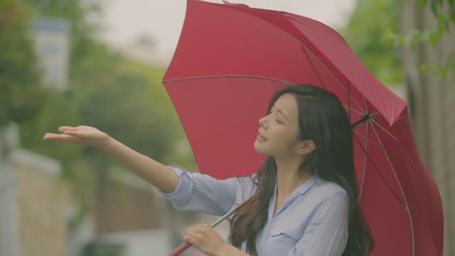 view of a woman with a red umbrella - umbrella stock videos and b-roll footage