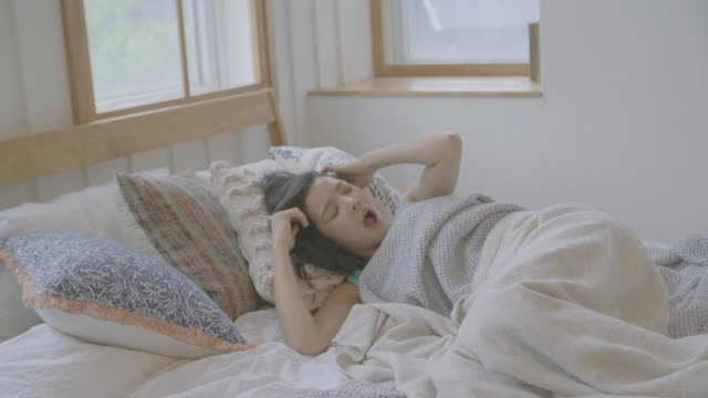 vidéos et rushes de view of a woman yawning and stretching out on bed - oreiller