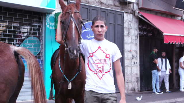 view of a young man with a horse waiting to renact the battle of kerbala during the ashura commerations in nabatieh ashura is the 10th day of... - ashura muharram stock videos & royalty-free footage