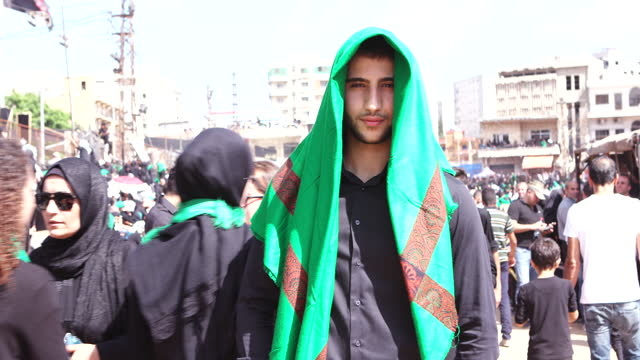 view of a young shia youth wearing a green scarf at the ashura commemorations in nabatieh. ashura is the 10th day of muharram commemorating the... - young men stock videos & royalty-free footage