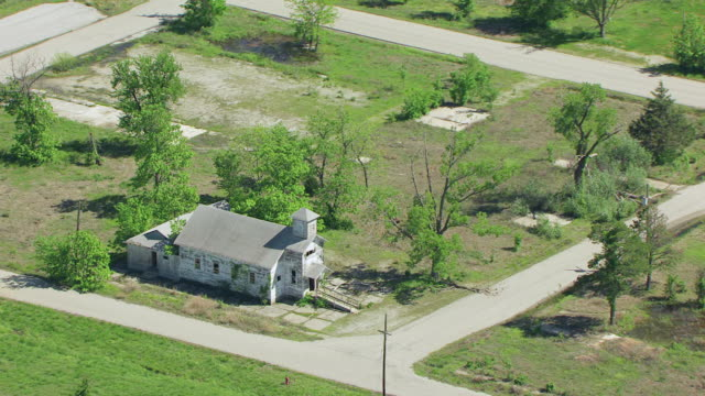 ws aerial zo view of abandoned christian church near chat pile at tar creek superfund site / picher, oklahoma, united states - oklahoma stock-videos und b-roll-filmmaterial