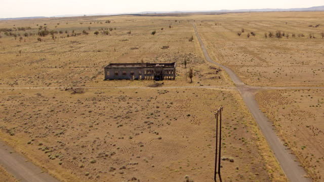 ws aerial zo view of abandoned hanford high school building surrounded empty desert at hanford site / richland, washington, united states - hanford nuclear reservation video stock e b–roll