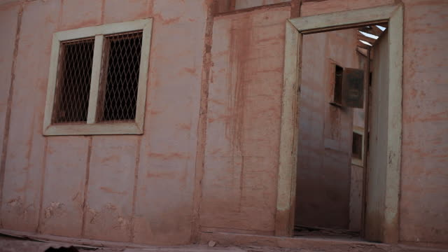 MS View of abandoned house with door closing in wind / San Pedro de Valdivia, Atacama desert, Chile