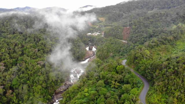 vidéos et rushes de vue de haut cascade dans la forêt profonde - eco tourism