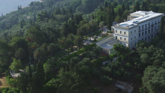ws aerial view of achilleion palace with ocean in backdrop / corfu, ionian islands, greece - palace stock videos & royalty-free footage