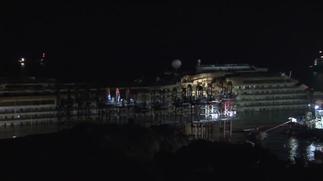 vídeos y material grabado en eventos de stock de ws pan view of across deck of costa concordia cruise ship surrounded by parbuckling equipment at night / giglio porto, tuscany, italy - crucero barco de pasajeros
