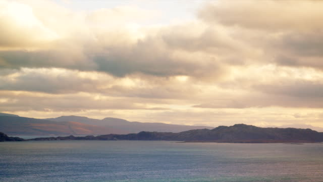 ws pan view of across sound of raasay with torridon hills with colorful clouds / skye island, scotland, united kingdom - isole ebridi video stock e b–roll