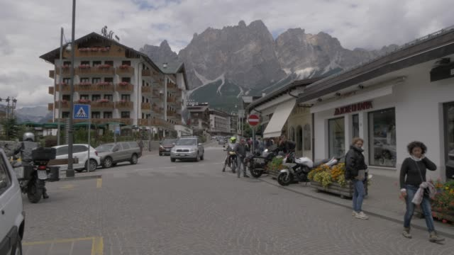 view of activity and mountains on main street in cortina d'ampezzo, belluno, dolomites, italy, europe - cortina stock videos & royalty-free footage