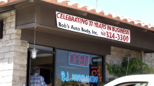 ms zi view of advertising sign board in auto body shop and powder coating services / cathedral city, california, usa  - spruchband stock-videos und b-roll-filmmaterial