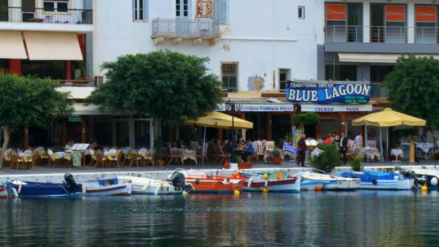 vídeos de stock, filmes e b-roll de ws view of agios nikolaos and boats at dock / greece - escrita ocidental