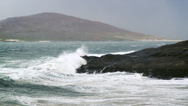 ms slo mo view of agitated waves breaking on shore rock with hills / harris island, scotland, united kingdom - 2k resolution stock videos and b-roll footage