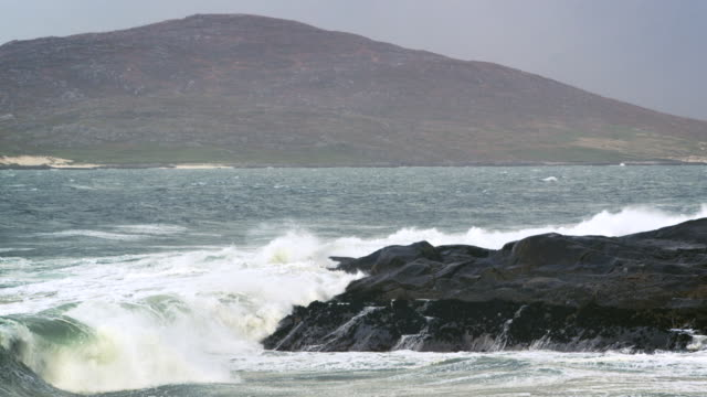 ms slo mo pan view of agitated waves breaking on shore rock with hills / harris island, scotland, united kingdom - 2k resolution stock videos and b-roll footage