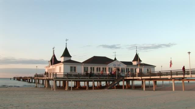ws view of ahlbeck pier at sunset  / ahlbeck, mecklenburg-western pomerania, germany - komplett stock-videos und b-roll-filmmaterial