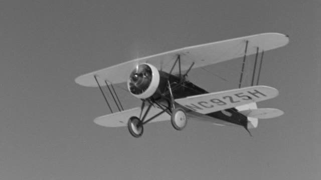 ws ts view of air to air shot of biplane in flight against cloudy sky and performing stunts and maneuvers - air to air shot stock videos & royalty-free footage