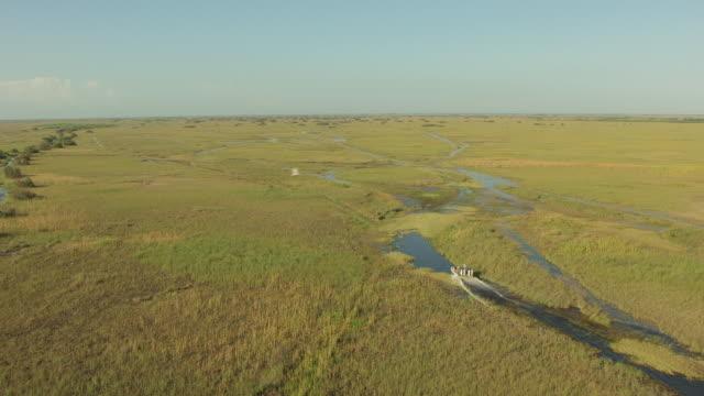 vídeos y material grabado en eventos de stock de ms aerial view of airboat moving through everglades / florida, united states - parque nacional everglades