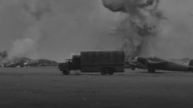ws view of airfield couple of airplanes on fire, more airplanes fly from back side over head battle field, war - bombardamento video stock e b–roll