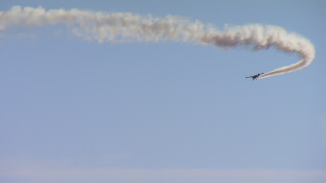 WS View of airplane flying in sky discharging smoke / United States