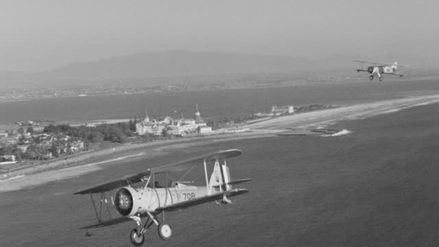 WS AERIAL TS View of airplane flying over San Diego coastline also air to air shots of biplanes in flight