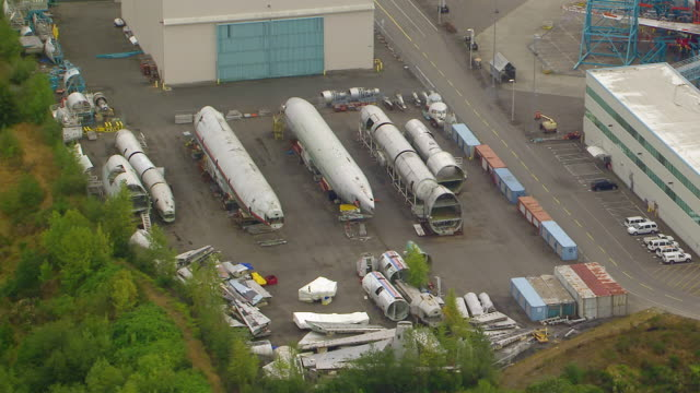WS AERIAL View of airplane fuselages and parts outside of Boeing Everett factory / Everett, Washington, United States